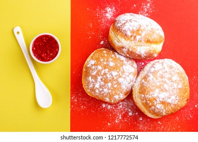 Tasty sweet sugary donuts with raspberry jam on bright yellow and red background. Traditional Jewish sweet Hanukkah dish. Copy space
