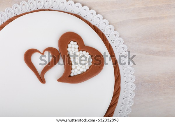 tasty sweet valentine love cake with hearts on wooden background