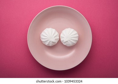 Tasty sweet zephyr on a white plate and pastel pink background. Funny concept smile