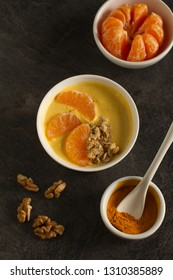 Tasty tangerine smoothie bowl with fruits, cereals, seeds and turmeric powder over  grey background