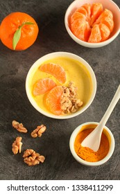 Tasty tangerine smoothie bowl with fruits, cereals, seeds and turmeric powder over grey background from above