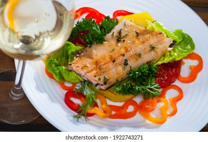 Tasty tender fried trout fillet served with bell pepper, tomatoes and greens on plate