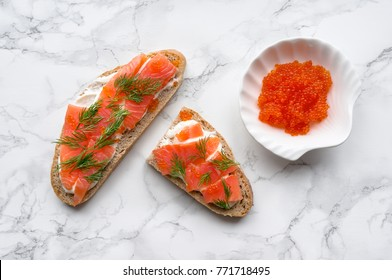 Tasty toast with salmon, caviar, cream cheese and dill on marble table. Healthy snack. Top view.