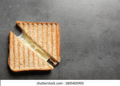 Tasty toast sandwiches with cheese on grey table, top view. Space for text