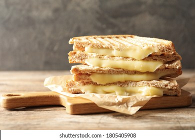 Tasty toast sandwiches with cheese on wooden table