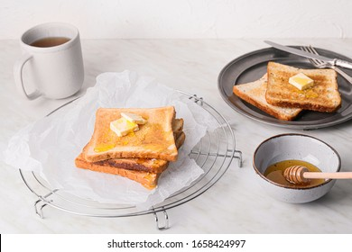 Tasty toasted bread with honey and butter on white background