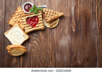 Tasty toasts with sweet jam and butter on wooden table