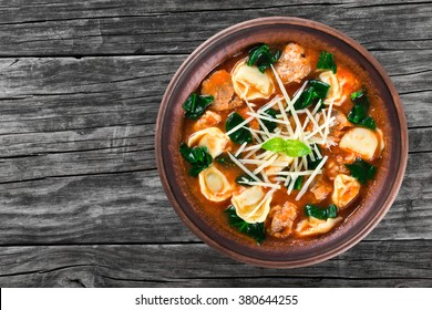tasty tortellini soup with italian sausages, spinach, tomato, shredded parmesan cheese and spices in a clay rustic bowl decorated with basil leaves, on an old table, top view