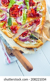 Tasty traditional Tarte Flambee from the Alsace region of France with a thin pastry crust topped with creme fraiche or cheese, onions, herbs, lardons and tomato sliced ready to serve as an appetizer