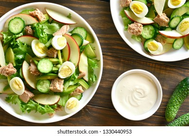 Tasty tuna salad with slices of cucumber, avocado, red apple and eggs in bowl on wooden background. Healthy diet food. Top view, flat lay