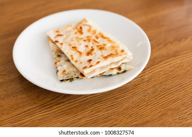 Tasty turkish gozleme: pita with cheese. Healthy nature food. Turkish traditional kitchen. Table in restaurant. Close up. Popular meal in Istanbul.