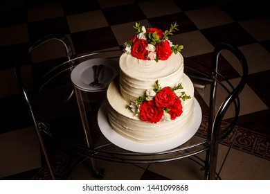 tasty two-tiered white creamy wedding cake with red and pink roses served on glass tray with plates and spoons