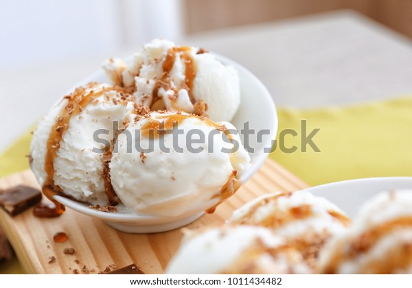 Tasty vanilla ice-cream balls with caramel topping in bowl on board