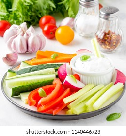 Tasty vegetable sticks of cucumber, pepper, carrots, celery and radishes with white sauce of sour cream, yogurt, herbs.