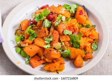 Tasty vegetarian dish - baked sweet potato with onions, carrots and basil leaves in a plate on the table, top view, close-up