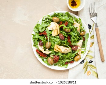 Tasty vegetarian salad with artichoke, rocket, sun-dried tomatoes and olives.