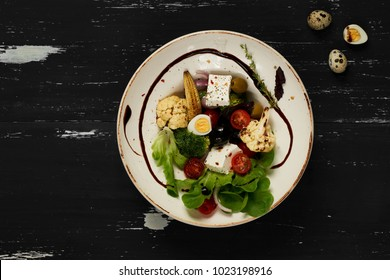 Tasty vegetarian salad made of quail eggs, lettuce, Feta cheese, broccoli, cauliflower, olives and baby corn on plate standing on blue old wooden table. Healthy dietary meal, wholesome dish. Top view.