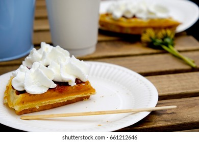 Tasty waffer with whipped cream and strawberry marmolade on a paper plate, lying on the wooden table with two dandelions. Summertime relax.