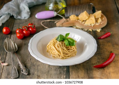 tasty and wholesome pasta, spaghetti or fettuccine for a hearty meal in a rustic design on the boards with or without sauce, with cherry and basil