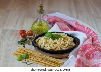 tasty and wholesome pasta, spaghetti or fettuccine for a hearty meal in a rustic design on the boards with or without sauce, with cherry and basil, in a rustic frying pan