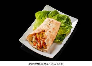 Tasty wrap sandwich on a plate with lettuce