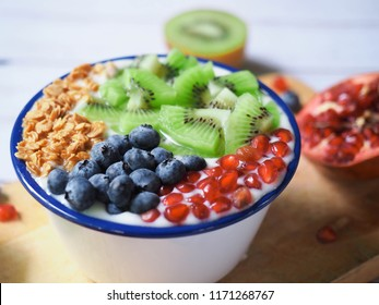 Tasty yoghurt with granola, blueberries, pomegranate and kiwi in bowl and wooden board on white wooden table. Healthy concept.
