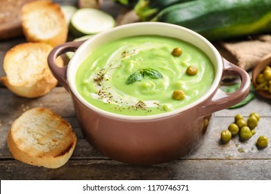 Tasty zucchini soup in saucepan on wooden table