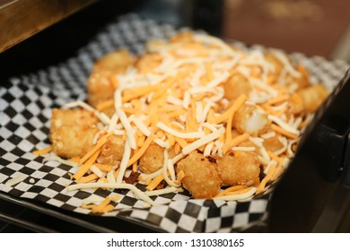 Tater tots covered with cheese and sprinkled bacon bits out of the oven.