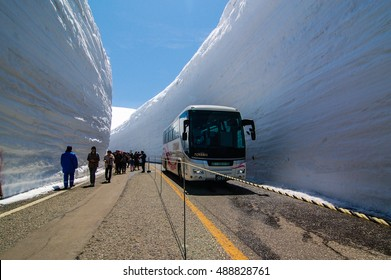 Tateyama, Japan-April 19, 2014: Tourists walk along the road with high snow wall in bright blue sky on sunshine at Murodo,Tateyama Kurobe Alpine Route beside a moving bus in seperated lane by the rope