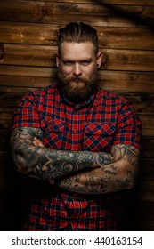 Tatooed  bearded male in a red shirt posing over wooden wall in a studio.