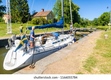 Tatorp, Sweden – July 3, 2018: Sailboat waiting for the sluice gate to be opened. Persons standing on boat holding ropes and the sluice guard is walking behind the boat towards the gate.