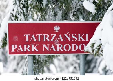 Tatra Mountains, Poland - February, 2006: forest inTatra National Park, board with text: Tatra National Park Poland