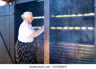 Tatra Mountains, Poland: July 30 2018 - A Polish farmer is making  oscypek cheese in Zakopane regions. Oscypek is made using salted sheep's milk, the final process is to be smoked in wood hut.