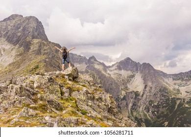 Tatry mountains landscape with a coming storm. A woman who enjoys climbing a mountain peak.