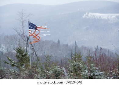 Tattered American flag blowing in the cold winter wind in a mountain landscape of Rangeley, Maine.