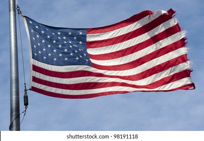 Tattered American flag flapping in the wind  on a blue sky with clouds