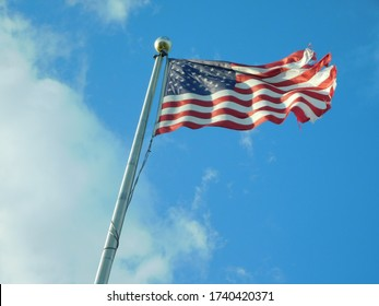 tattered American flag on flagpole blowing in the wind against a bright blue sky with puffy clouds