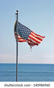 Tattered American flag waving over a blue sea