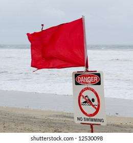 Tattered red flag flying in the wind and warning sign saying danger, no swimming, beach closed, on a stormy day at the beach with big waves.