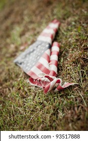 A tattered and torn American flag on the ground.