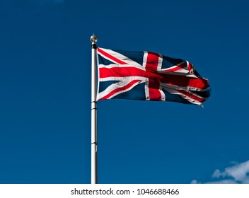 Tattered Union Flag or Union Jack flies in stiff breeze against blue sky