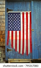Tattered and weathered American flag tacked on to a blue wood door to a distressed cabin on the coat of maine