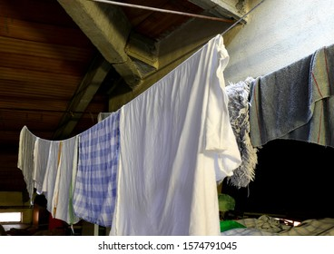 tatters and rags on the washing lines inside an wide attic