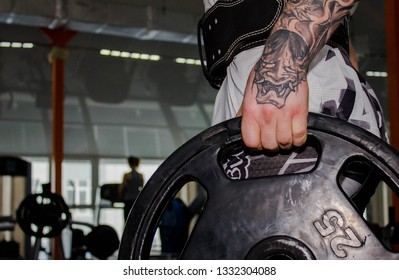 Tattoed hand of MMA young fighter holding heavy weight disc, plate for barbell in gym. MMA training program. Weightlifting in a power lifting belt, powerlifting. Lifestyle, healthy, sport. Stylish.