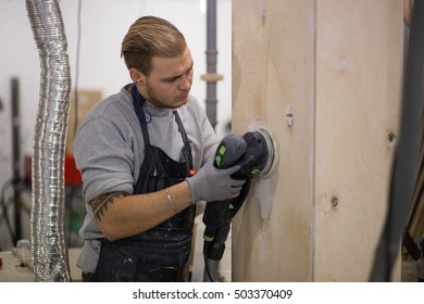 tattoed man polishes boards. carpenter with a sander