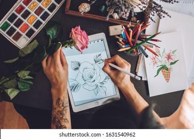 Tattoo art digital process on ipad. Tattoo artist hands holding Apple Pencil and drawing on iPad Pro in Procreate. Kropivnitskiy, Ukraine, September 27, 2019.