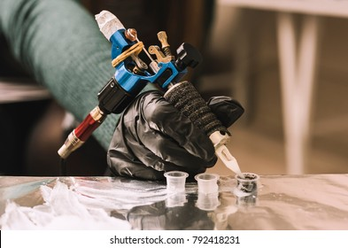 Tattoo artist holding a tattoo machine in black sterile gloves. Master tattoo draws paint on the clients tattoo.