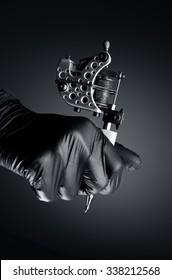 Tattoo artist holding tattoo machine, Machine for a tattoo concept dark background,tattoo machine in hand