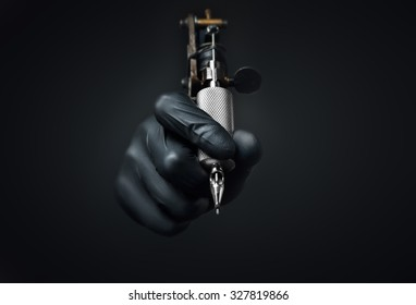 Tattoo artist holding tattoo machine on dark background, Machine for a tattoo concept