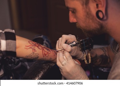 Tattoo artist is inserting ink into the skin using sterilized nitrile gloves and tattoo machine